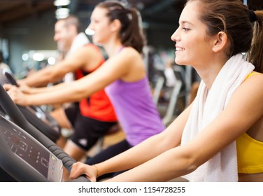 Smiling woman doing indoor biking in a fitness club
