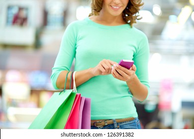 Smiling woman doing shopping and texting on the way