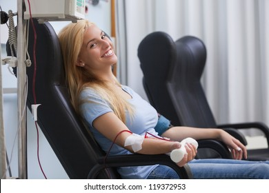 Smiling woman donating blood in hospital