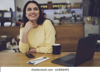 Smiling woman dreaming about opening own cafeteria with modern design and sweet cakes. Beautiful young entrepreneur planning work in business industry sitting indoors during rest and enjoying coffee