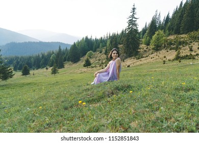 smiling woman in dress sitting on grass at pine forest
