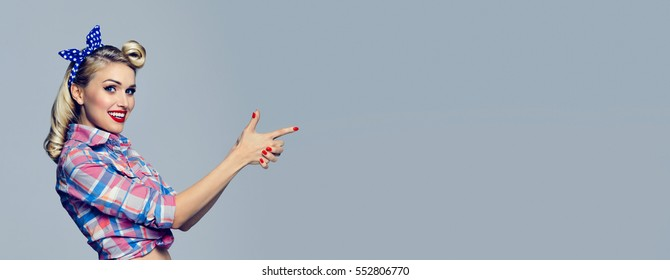 Smiling woman, dressed in pin-up style, showing something or copyspace area for text or slogan. Caucasian blond model posing in retro fashion and vintage concept shoot. Horizontal banner composition.
