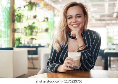 Smiling woman drinking a cocktail while spending her time in a modern cafe, sitting at the desk, touching her chin with a hand. White beautiful smile