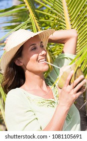 smiling woman drinking a coconut with a straw on the beach in summer