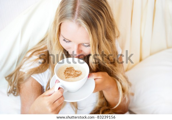 Smiling woman drinking a coffee lying on a bed at home or hotel. Heart shape illustrated on coffee foam. Horizontal shot. Model is breathing aromatic smell of her coffee. Lots of Copyspace.