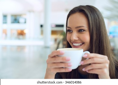 Smiling woman drinking coffee in the morning at restaurant soft focus. Closeup portrait of a pretty young lady
