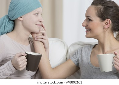 Smiling woman drinking coffee and taking care of friend during chemotherapy