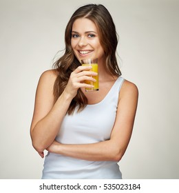 smiling woman drinking orange juice with glass studio isolated portrait.