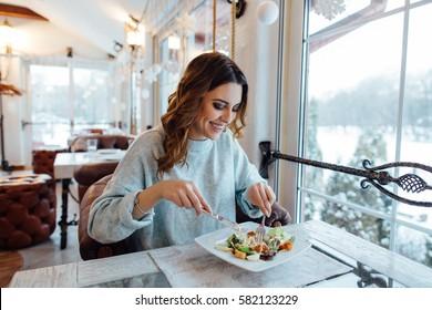 Lächelnde Frau, die frisch Salat im Restaurant isst