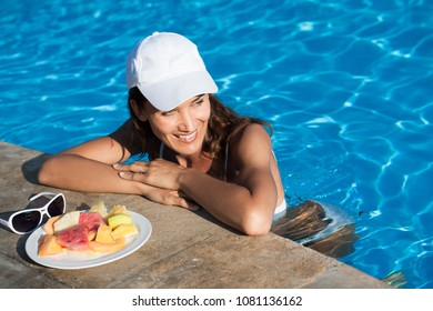 smiling woman eating fruit in a swimming pool