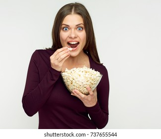 Smiling woman eating pop corn from glass bowl. Isolated portrait on white.