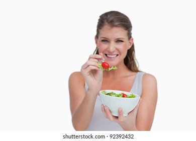 Smiling woman eating a salad against a white background