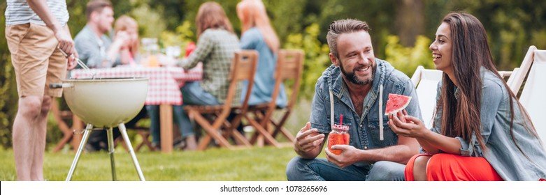 Smiling woman eating watermelon and her  friend drinking juice during garden party