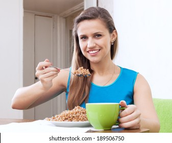 Smiling woman eats buckwheat cereal with spoon at home