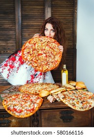 Smiling woman eats large pizza. Too much food. Diet concept. Gluten, fat and weight loss problem