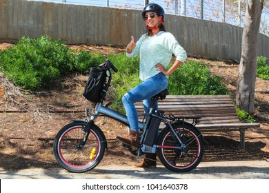 A smiling woman with electric bicycle in the park with a helmet