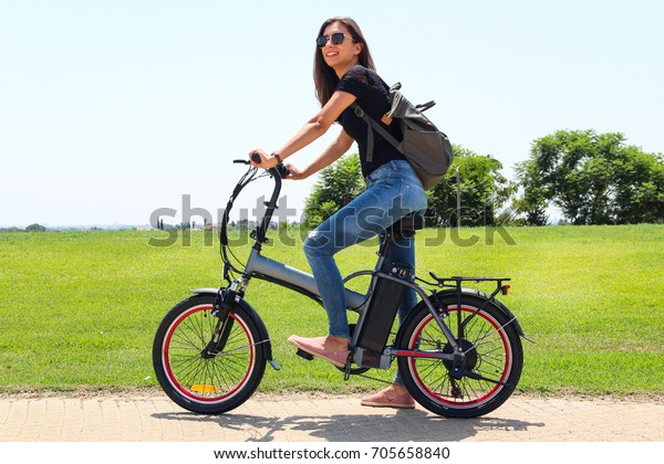 A smiling woman with electric bicycle  in the park