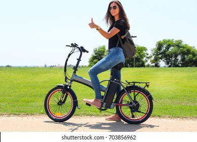 A smiling woman with electric bike in the park Makes a like with her hand