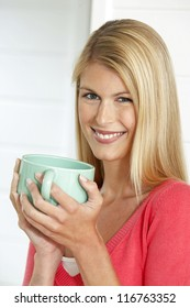 Smiling woman enjoying a large cup of hot soup which she is cradling in her hands