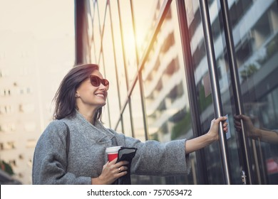 Smiling woman entering in the building. Happy businesswoman getting to work and entering in office building.
