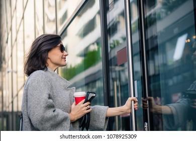 Lächelnde Frau, die in Wohngebäude eintritt. Gute Geschäftsfrau kommt zur Arbeit und geht in das Bürogebäude.