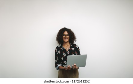 Smiling woman entrepreneur holding a laptop standing against a white background. Portrait of a businesswoman standing with an open laptop.