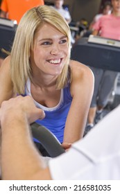 Smiling woman exercising in health club