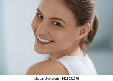Smiling woman face with white teeth, smile, clean skin and natural makeup closeup portrait on light background