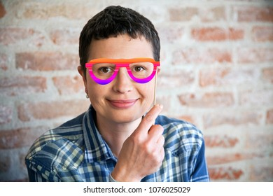 Smiling woman with fake colored eyeglasses