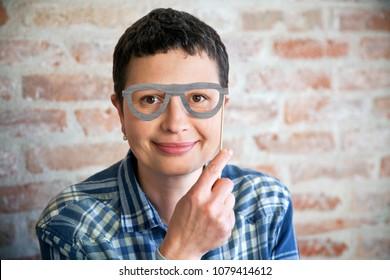 Smiling woman with fake eyeglasses