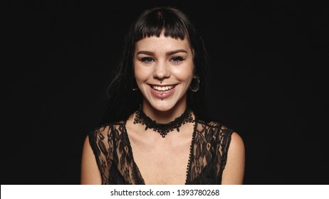 Smiling woman with fashion piercing on lips isolated on black background. Portrait of a young gothic woman looking at camera.