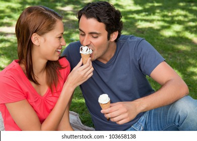 Smiling woman feeding her friend an ice cream cone as they sit next to each other on the grass