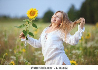 Smiling woman in the field in the morning, she is holding a sunflower flower in her hand.