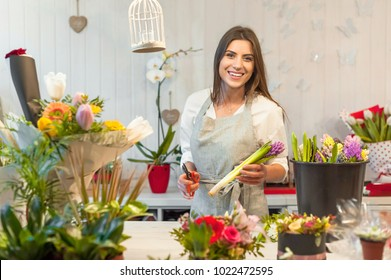 Smiling woman florist small business flower shop owner, at counter holding a scissor cuting hyacinths, making arrangements and smiling at camera.