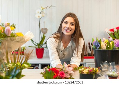 Smiling woman florist small business flower shop owner, at counter, looking frinedly at camera.