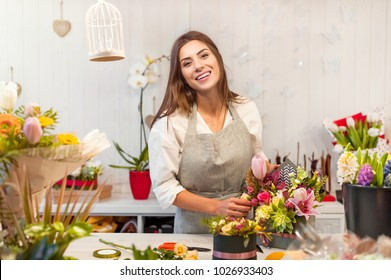 Smiling woman florist, small business flower shop owner, at counter, looking friendly at camera working at a special flower arrangement.