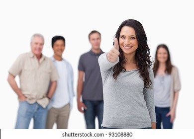 Smiling woman with friends behind her giving thumb up against a white background