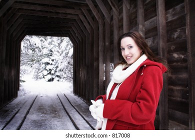 Smiling woman in front of covered bridge in the snow
