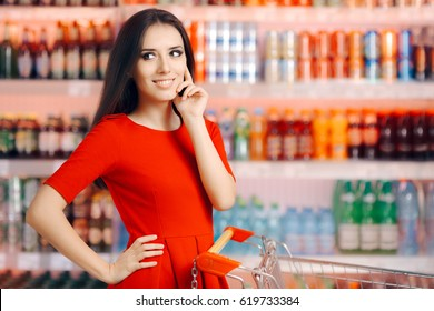 Smiling Woman in Front of the Soda and Refreshing Beverages Shelf - Shopper in a supermarket with a shopping cart choosing fresh drinks
