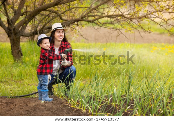 smiling woman gardener with little boy watering vegetable garden with hose. Happy family spending time together doing hobby outdoors