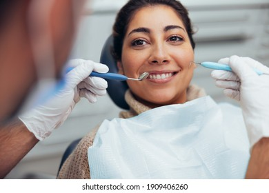 Smiling woman getting her teeth checked by dentist. Female having dental checkup in clinic.
