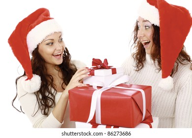 Smiling woman giving xmas presents to her friend or sister isolated on white background. Excitement and happiness.
