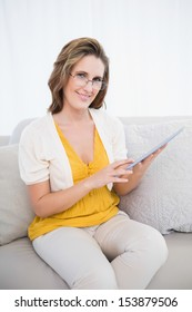 Smiling woman with glasses using tablet computer looking at camera