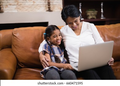 Smiling woman with granddaughter using laptop while sitting on sofa at home