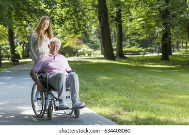Smiling woman with grandfather on a wheelchair during walk in the park