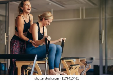 Smiling woman at the gym doing pilates training with her trainer. Trainer helping woman in pulling the stretch bands while doing pilates workout.