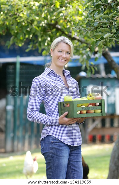 Smiling woman harvesting apples