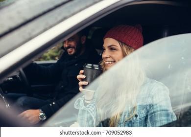Smiling woman having a coffee with man driving the car. Young couple on road trip.