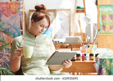 Smiling woman having cup of coffee and reading article on digital tablet in studio