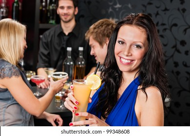 Smiling woman having drink with friends at cocktail bar